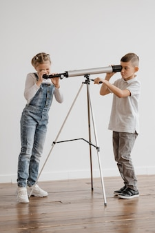 Crianças usando telescópio na aula
