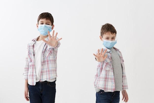Crianças vestindo máscaras médicas, mostrando as mãos limpas