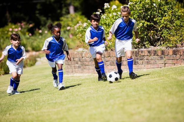 Crianças vestindo uniforme de futebol jogando uma partida