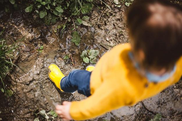 Criancinha, usando botas de chuva amarela, jogando na lama