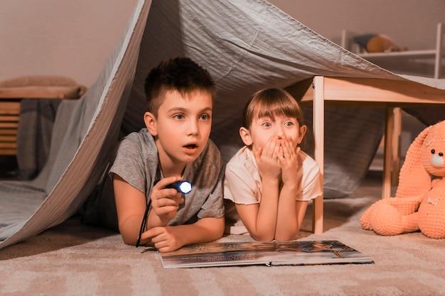 Criancinhas assustadas lendo histórias para dormir em casa