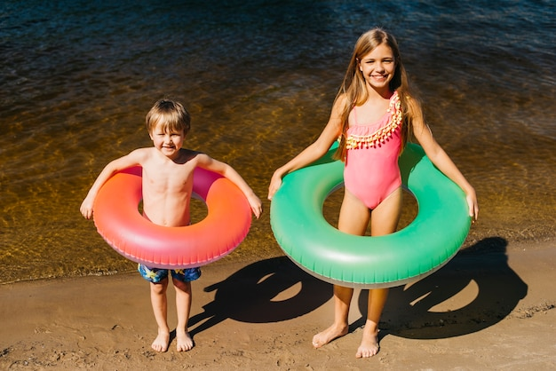 Criancinhas com anéis de natação na praia