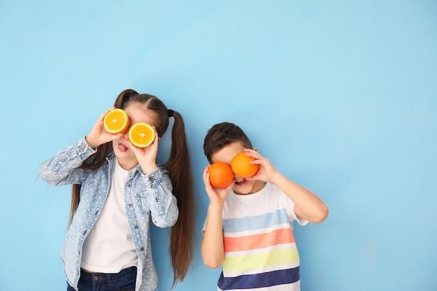 Criancinhas engraçadas com frutas cítricas coloridas