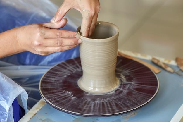 Criando jarra ou vaso de barro. mãos de mulher, roda de oleiro