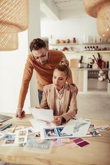 Criando juntos. concentrado e bonito estilista e sua bela assistente trabalhando em sua nova coleção.