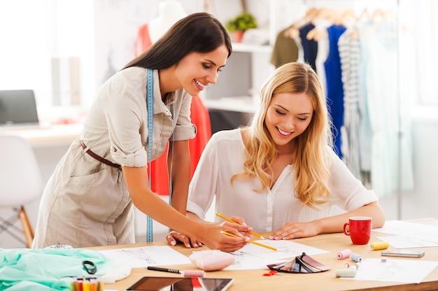 Criando seus novos designs. duas jovens felizes trabalhando juntas em sua oficina de moda