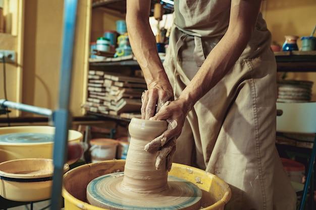 Criando um pote ou vaso de argila branca close-up. mestre pote. mãos de homem fazendo macro de jarro de barro.
