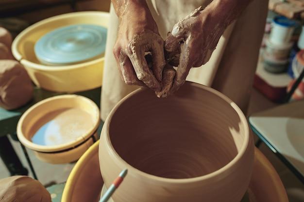 Criando um pote ou vaso de argila branca close-up. mestre pote.