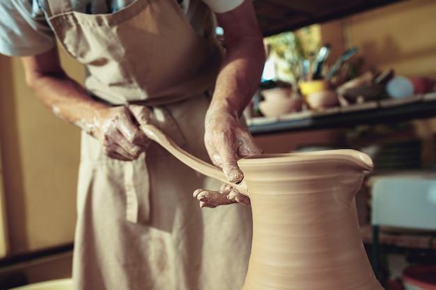 Criando um pote ou vaso de argila branca close-up.