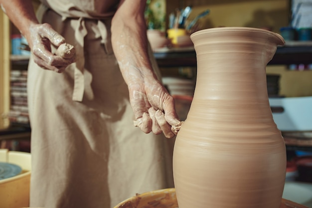 Criando uma jarra ou vaso de close-up de argila branca. mestre crock. mãos de homem fazendo macro de jarro de barro. o escultor na oficina faz uma jarra com um close de cerâmica. roda de oleiro torcida.