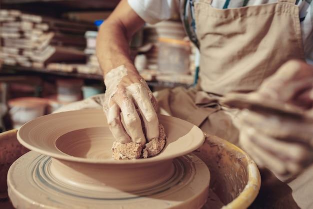 Criando uma jarra ou vaso de close-up de argila branca. mestre crock. mãos de homem fazendo macro de jarro de barro.