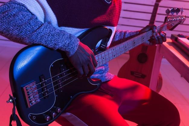 Criar música e um conceito de estúdio de gravação - guitarrista afro-americano gravando baixo elétrico