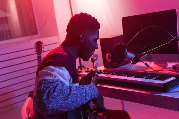 Criar música e um conceito de estúdio de gravação - guitarrista afro-americano gravando elétrico