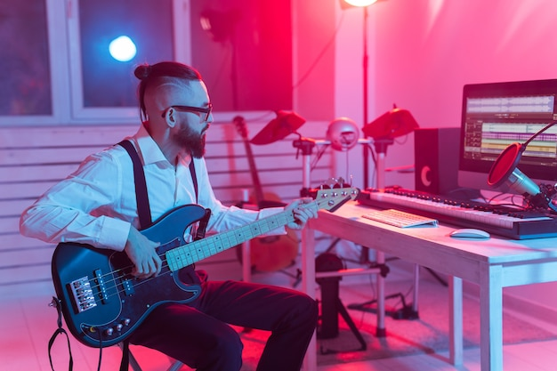Criar música e um conceito de estúdio de gravação - guitarrista de homem barbudo gravando faixa de guitarra elétrica