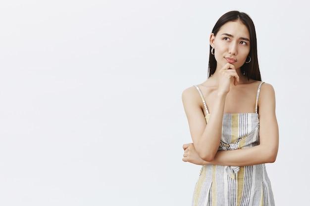 Criativa e atraente designer feminina asiática de roupas em trajes combinando, segurando a mão no queixo, parecendo sonhadora enquanto pensa em ideias ou planejando algo, parada pensativa sobre uma parede cinza