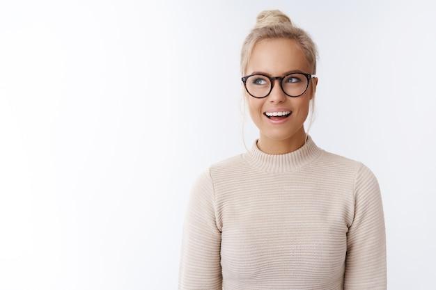 Criativa e feliz atraente loira de cabelos loiros caucasiana de suéter e óculos, tendo uma ideia interessante e incrível, olhando para o canto superior esquerdo, sonhando acordada, sorrindo satisfeita sobre a parede branca