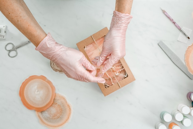 Criatividade e habilidade. uma jovem cria bases para copos de resina. embalagem de presente. embalagem decorativa. ideia para negócios. trabalho remoto, trabalho em casa. porta-copos de arte.