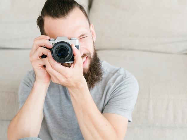 Criatividade e inspiração do passatempo. lazer e estilo de vida do fotógrafo. homem segurando a câmera fotográfica nas mãos e olhando através da lente.