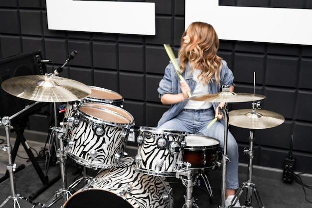 Criatividade e música. jovem menina bonita toca bateria. estúdio de gravação. equipamento musical.