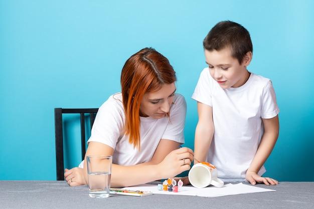 Criatividade infantil. mãe e filho pintando em azul