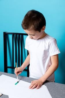 Criatividade infantil. menino pintando com tinta sobre fundo azul, vista superior