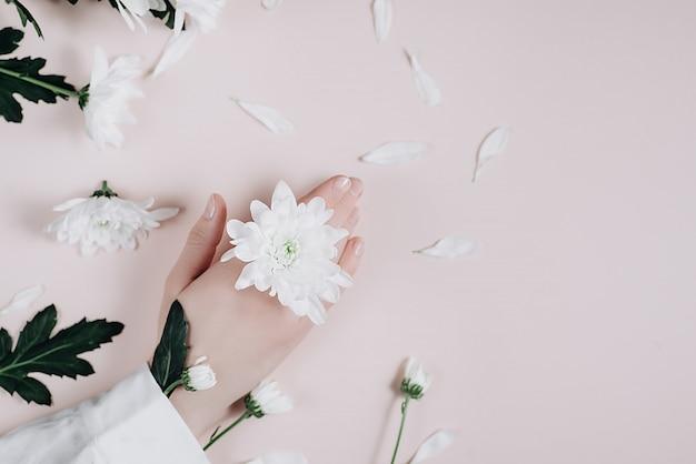 Criativo e moda arte pele cuidados de mãos e flores brancas na mão das mulheres.