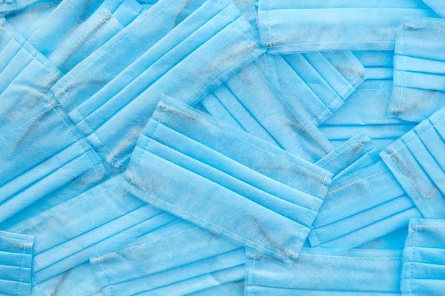 Criativo médico de máscaras azuis protetoras antibacterianas caoticamente dispostas. conceito de prevenção de doenças respiratórias e vírus.