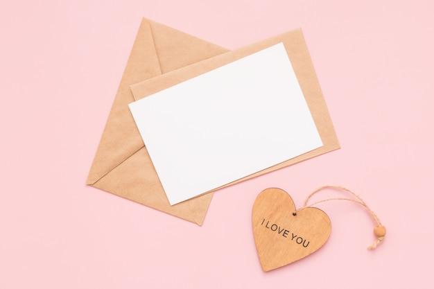 Crie envelopes, cartão branco de papel em branco e coração de madeira com as palavras eu te amo em uma parede rosa. lugar para texto. postura plana. vista do topo. feliz dia dos namorados.