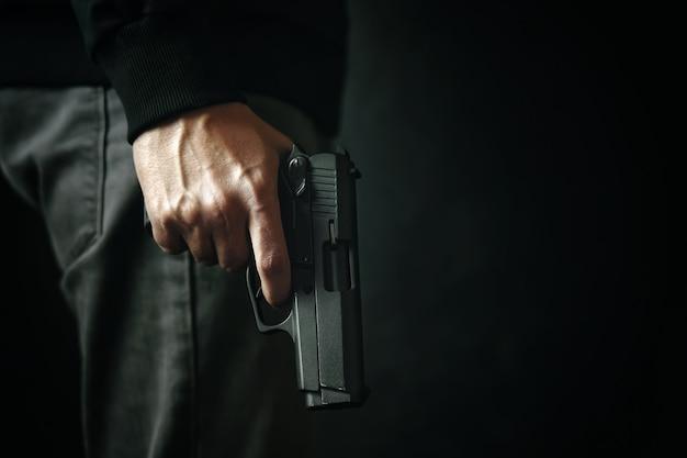 Criminoso com revólver na arma de fogo de fundo escuro na defesa da mão do homem ou assassino de ataque ou armado.