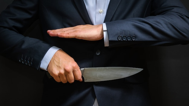 Criminoso com uma grande faca escondida. arma fria, roubo, homicídio.