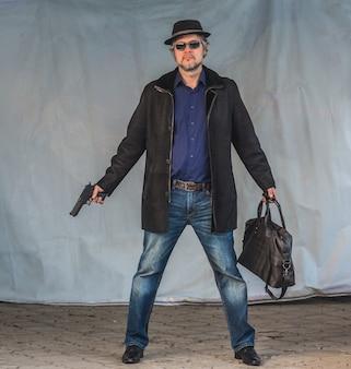 Criminoso masculino com uma arma e um saco