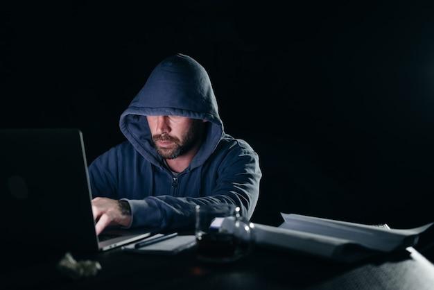 Criminoso misterioso em um capuz hackeando um laptop no escuro