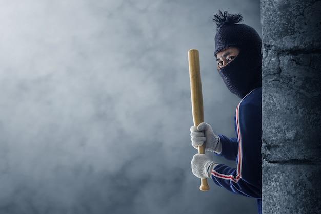 Criminoso ou bandido segurando um taco de beisebol.
