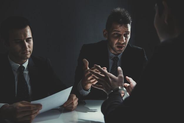 Criminoso sendo entrevistado em interrogatório