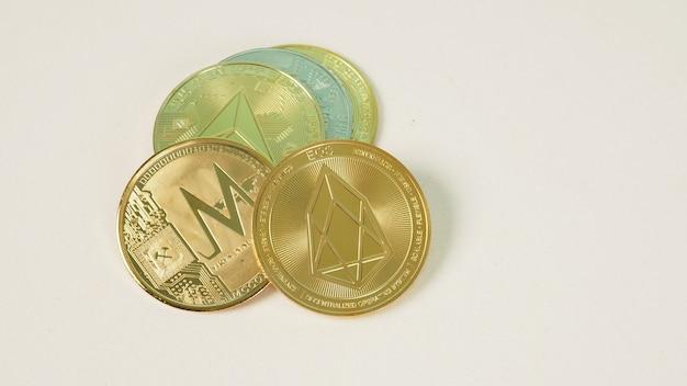 Criptomoeda com várias moedas de símbolo de criptomoedas físicas prateadas e douradas brilhantes em fundo branco