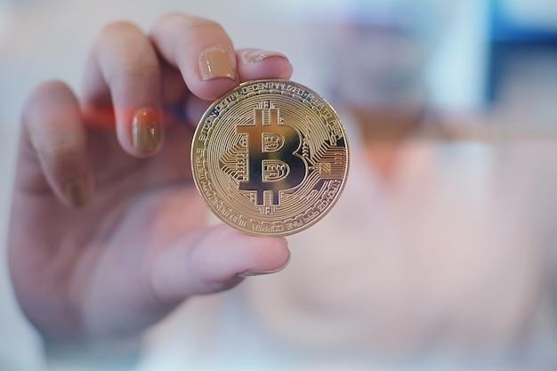 Criptomoeda de bitcoin dourado com a mão