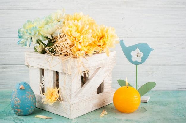 Crisântemo azul e amarelo em caixa de madeira branca