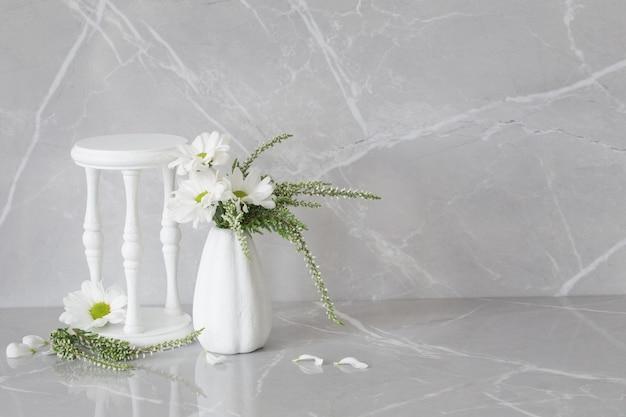 Crisântemos brancos em um vaso a sobre fundo de mármore cinza