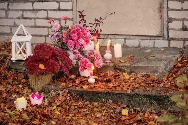 Crisântemos com velas em chamas no jardim outono