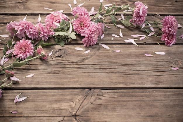 Crisântemos rosa em madeira escura