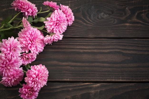 Crisântemos rosa sobre fundo escuro de madeira