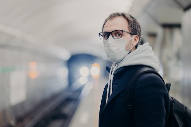 Crise de coronavírus. o homem segue as regras de quarentena, usa máscara médica protetora, viaja nos transportes públicos e se preocupa com a saúde durante epidemia ou pandemia. perigo de pegar vírus no transporte da cidade