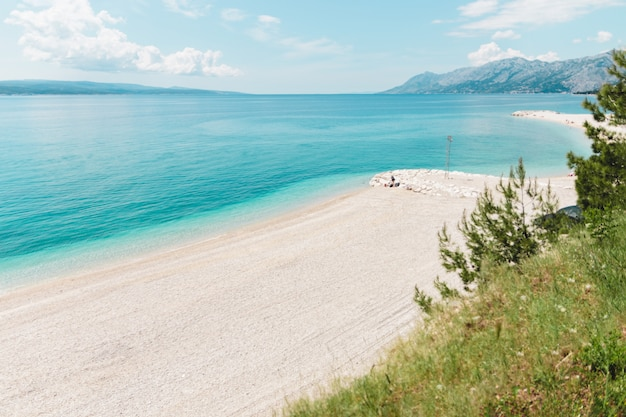 Crise do turismo em 2020. praia grande vazia com vista para a montanha na croácia no verão