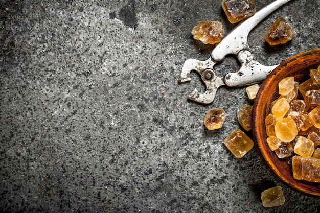 Cristais de açúcar de cana em uma tigela. sobre um fundo rústico.