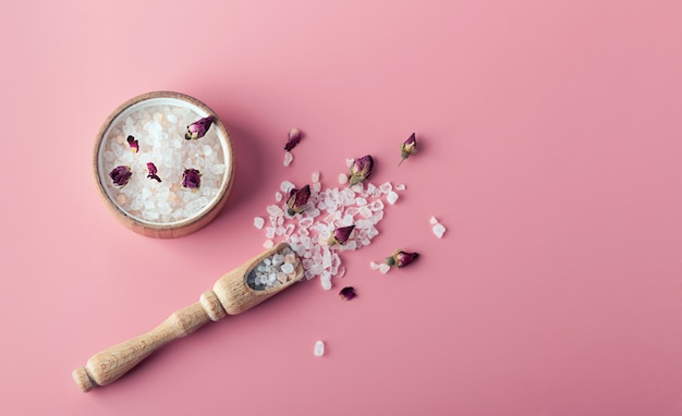 Cristais de sal para spa e banho estão espalhados em um fundo rosa com espaço de cópia. óleo essencial com pétalas de rosas e botões. o conceito de medicina alternativa, relaxamento, respiração corporal