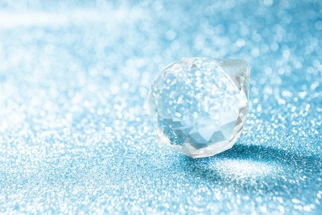Cristal transparente em forma de bola em um azul brilhante com bokeh