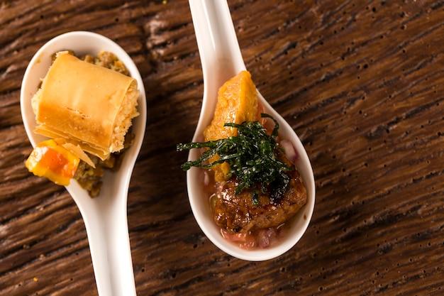 Crocante com mousse de queijo, acompanhado de castanha de caju com castanha de caju e mignon de porco com cremosa canjiquinha e vinagrete à colher. prove petiscos gastronômicos