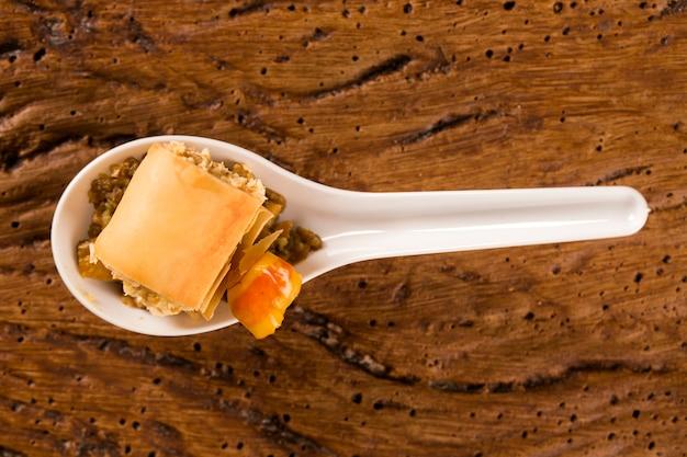 Crocante com mousse de queijo, acompanhado de castanha de caju e castanha de caju numa colher. prove petiscos gastronômicos