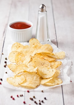 Crocante deliciosa pimenta batatas fritas chips lanche na placa de madeira branca com molho e sal