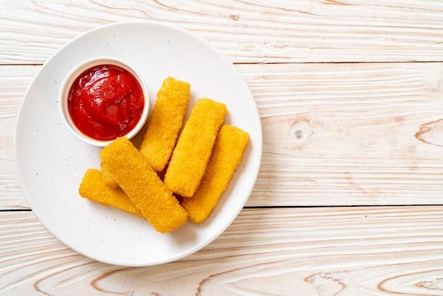 Crocantes de peixe frito com migalhas de pão servidos no prato com ketchup